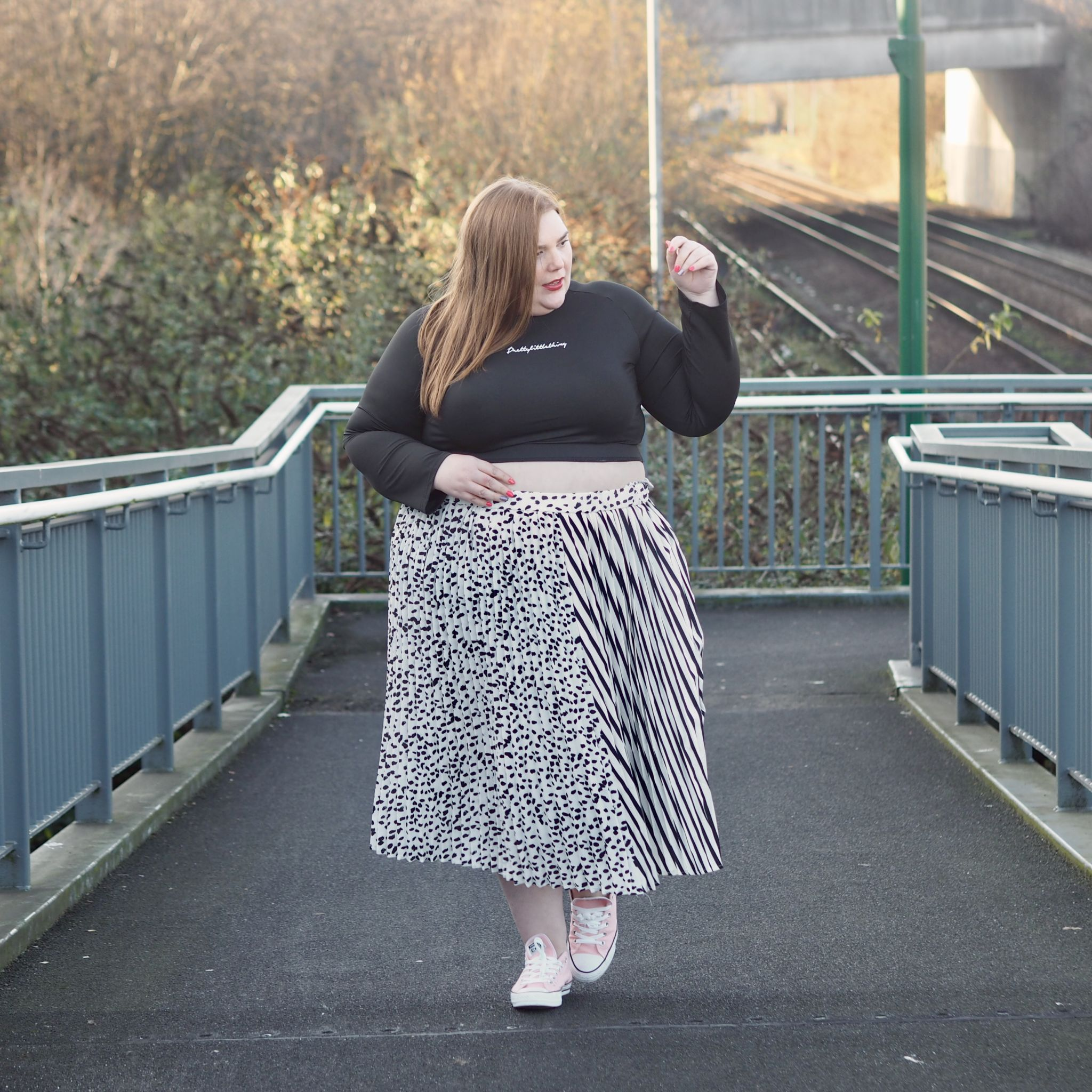Plus size model wearing black crop top and a floaty black and white mixed print skirt and pink converse trainers